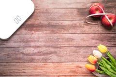 Numérique blanc d'échelle de poids avec le grippage rouge de pomme de régime avec la bande de mesure sur le concept en bois de la Photographie stock
