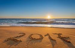 Numéro 2017 écrit sur le sable de bord de la mer au lever de soleil Image libre de droits