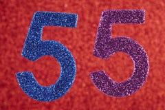 Numéro cinquante-cinq pourpres bleus au-dessus d'un fond rouge anniversaire Images libres de droits