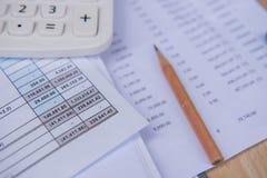 Numéro de comptes de plan rapproché sur un papier, une calculatrice et un crayon imprimés Image stock