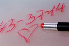 Numéro de téléphone écrit par le rouge à lèvres sur le verre Photos stock