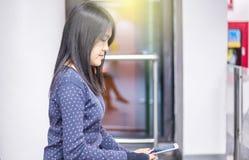 Numéro de vol de vérification de femme sur le téléphone portable dans l'aéroport Image stock