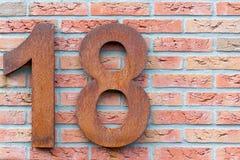 Numéro dix-huit en rouge sur un mur de briques Photos stock