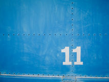 Numéro onze dans le blanc avec le fond et les rivets bleus Photographie stock