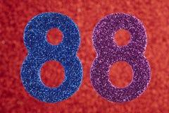 Numéro quatre-vingt-huit pourpres bleus au-dessus d'un fond rouge Anniversa Photo stock