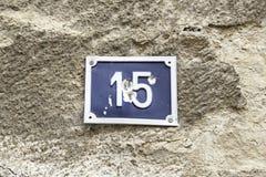 Numéro quinze sur un mur d'une maison photos stock