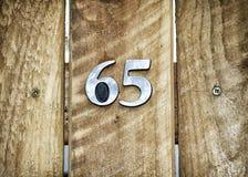Numéro soixante-cinq sur la porte en bois images libres de droits
