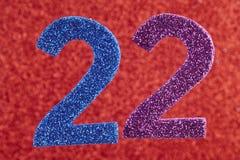 Numéro vingt-deux pourpres bleus au-dessus d'un fond rouge anniversaire Images libres de droits