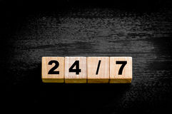 Numéros 24/7 d'isolement sur le fond noir Image stock