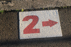 Number 2 in white on footpath. The Number two in red and white on the path Royalty Free Stock Images