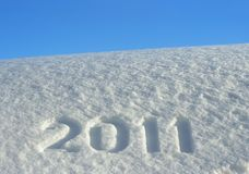 Number 2011 on snowdrift. Number 2011, written on snowdrift and blue sky, New Year's background royalty free stock photo