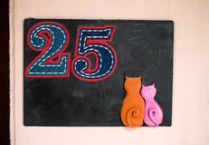 Number 25. Number twenty five in stitched denim on a blackboard with cats Stock Photos