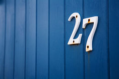 Number 27. Close up of the number twenty seven on the side of a blue beach hut Stock Photos
