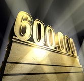 Number 600.000. Number six hundred thousand in golden letters on a golden pedestal Stock Photography