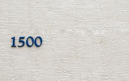 The number 1500 against a stucco wall. Digits comprising the number 1500 on a beige stucco wall with copy space royalty free stock image