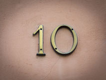 Number 10 background. Gold house number ten on a pink background Royalty Free Stock Images