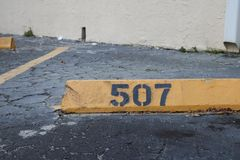 Number 507 black on yellow. asphalt on the background. black number stencil painted on backdrop, number 507; number five hundred s stock images