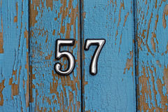 Number 57 on blue wooden wall with peeling paint Royalty Free Stock Photos