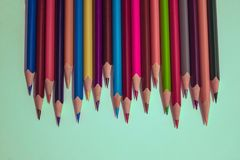We are ready!. A number of bright, sharply sharpened pencils of different colors. Brainstorming, task for creativity of thinking, teamwork. Light background, top Stock Photos