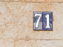 Number 71 on ceramics. White number 71 on blue ceramic surface - house number Stock Image