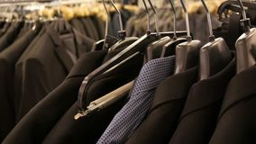 A number of different fashionable men`s black jackets and shirts on the hanger in the men`s clothing store in the. Shopping center stock video