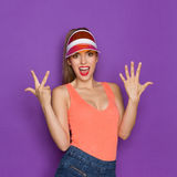 Number Eight. Excited girl in orange shirt and sun visor showing eight fingers. Waist up studio shot on violet background Stock Photo