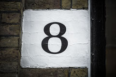 Number eight hand painted on plaster background Stock Photos