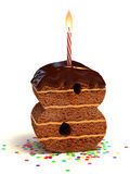 Number eight shape birthday cake. Number eight shaped chocolate birthday cake with lit candle and confetti Stock Photos