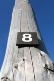 Number eight. On the wooden post Stock Photography