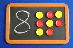 A number eight written on a black board. With the same quantity showed by colorful round tokens royalty free stock photos