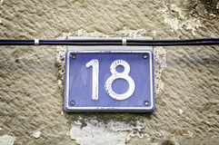Number eighteen. Detail of a number on a wall in the city, and figures signal Royalty Free Stock Photo