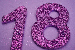 Number eighteen purple color over a purple background. Anniversa Stock Photography