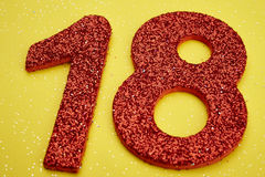 Number eighteen red color over a yellow background. Anniversary Stock Photos