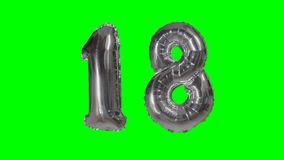 Number 18 eighteen years birthday anniversary silver balloon floating on green screen -. Number 18 eighteen years birthday anniversary silver balloon floating on stock video