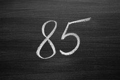 Number eighty five enumeration written with a chalk on the blackboard. Closeup view Stock Images