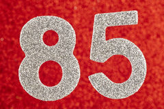 Number eighty-five silver color over a red background. Anniversa Stock Photo