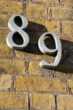 Number eighty nine on exterior wall in strong sunshine stock images