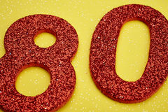 Number eighty red color over a yellow background. Anniversary Royalty Free Stock Photography