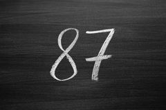 Number eighty seven enumeration written with a chalk on the blackboard Stock Photos