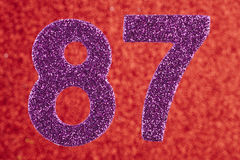 Number eighty-seven purple color over a red background. Annivers Royalty Free Stock Images