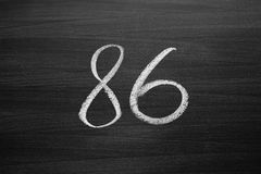 Number eighty six enumeration written with a chalk on the blackboard Stock Photography