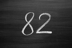 Number eighty two enumeration written with a chalk on the blackboard. Closeup view Stock Photography