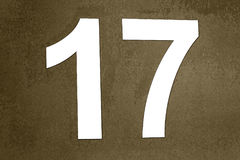 Number 17 Engraved   in white wall. Label number 17 in white wall stuck on dirty or degraded digital background Royalty Free Stock Photos