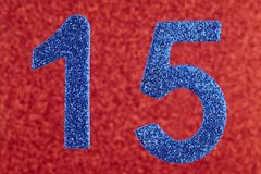 Number fifteen blue color over a red background. Anniversary. Stock Photo
