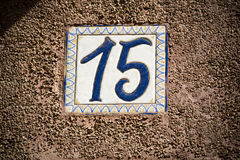Number fifteen enamelled door number on plaster wall Stock Image