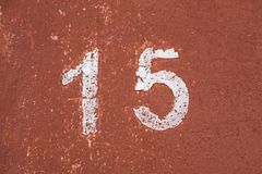 The number fifteen in white on an old red wall. Number fifteen on the old wall of red color Stock Photography
