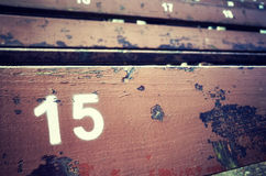 Number fifteen painted on an old wooden seat. Stock Images