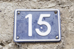 Number fifteen in a wall of a house. Detail of a number of information, odd number Royalty Free Stock Photo