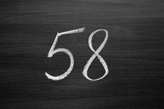 Number fifty eight enumeration written with a chalk on the blackboard. Closeup view Stock Images
