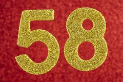 Number fifty-eight gold color over a red background. Anniversary stock image